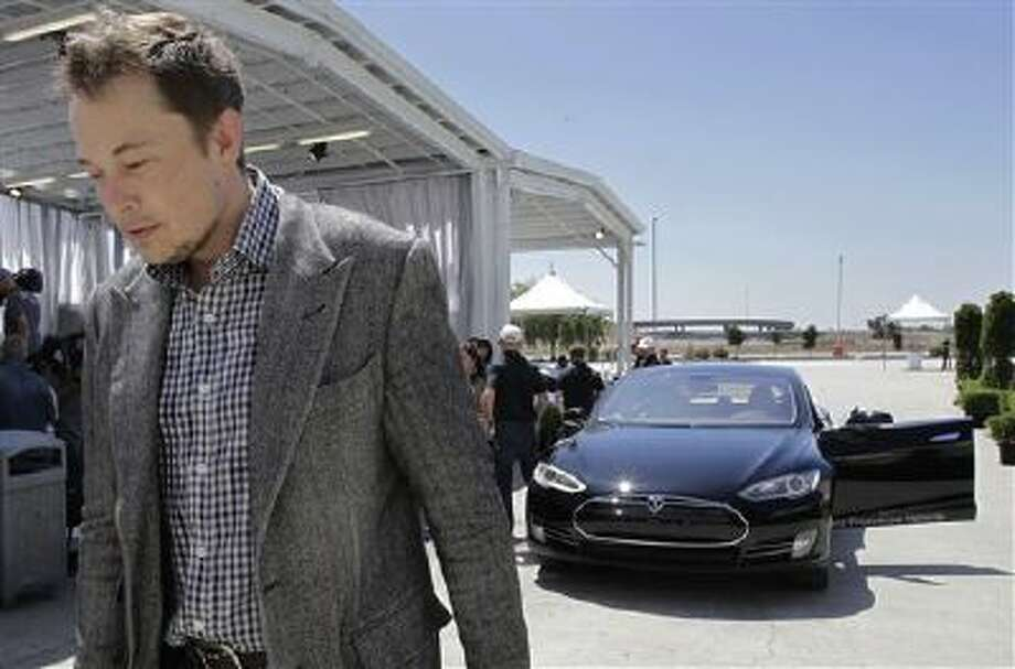In this Friday, June 22, 2012 file photo, Tesla CEO Elon Musk walks past the Tesla Model S after a news conference at the Tesla factory in Fremont, Calif. Photo: AP / AP