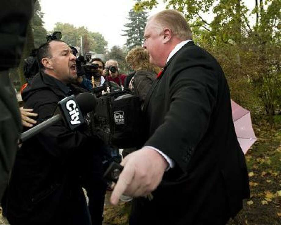 Toronto Mayor Rob Ford tells to the media to get off his property as he leaves his home in Toronto on Thursday, Oct. 31, 2013. A judge on Wednesday ordered the release of police documents in the drug case against a friend of Ford. Peter Jacobsen, a lawyer for various Canadian news organizations that pushed to release the records, said the case against Alexander Lisi involves the mayor. (AP Photo/, Nathan Denette) Photo: AP / The Canadian Press