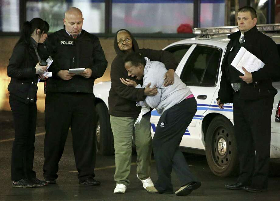Toni Martin, front center, cries out on Dec. 24, 2014 as she talks to police at the scene where she says her son was fatally shot Tuesday at a gas station in Berkeley, Mo. Authorities did not immediately identify the man who was shot. But the St. Louis Post-Dispatch reported that Toni Martin, said he was her son, Antonio Martin. Photo: AP Photo/St. Louis Post-Dispatch, David Carson  / St. Louis Post-Dispatch