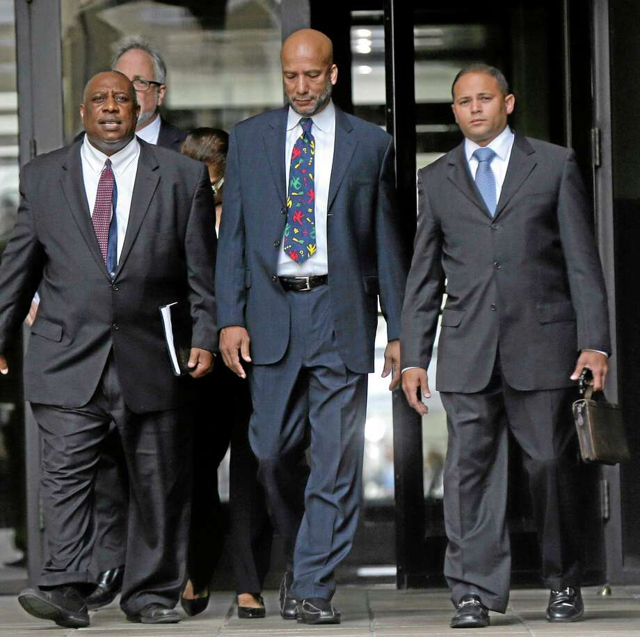 Former New Orleans Mayor Ray Nagin, center, leaves federal court after being sentenced in New Orleans, Wednesday, July 9, 2014.  Nagin was sentenced Wednesday to 10 years in prison for bribery, money laundering and other corruption that spanned his two terms as mayor, including the chaotic years after Hurricane Katrina hit in 2005. He was convicted Feb. 12 of accepting hundreds of thousands of dollars from businessmen who wanted work from the city or Nagin's support for various projects. The bribes came in the form of money, free vacations and truckloads of free granite for his family business. (AP Photo/Gerald Herbert) Photo: AP / AP