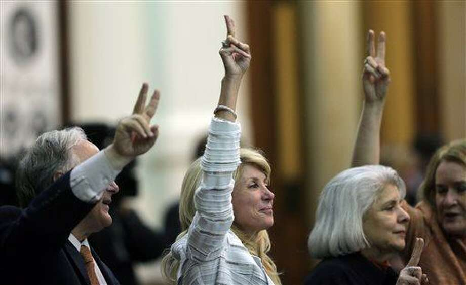 """Sen. Wendy Davis, D-Fort Worth, center, holds up two fingers to signal a """"No"""" vote as the session where they tried to filibuster an abortion bill draws to a close, Tuesday, June 25, 2013, in Austin, Texas. Despite barely beating a midnight deadline, hundreds of jeering protesters helped stop Texas lawmakers from  passing the abortion bill.  (AP Photo/Eric Gay) Photo: AP / AP"""