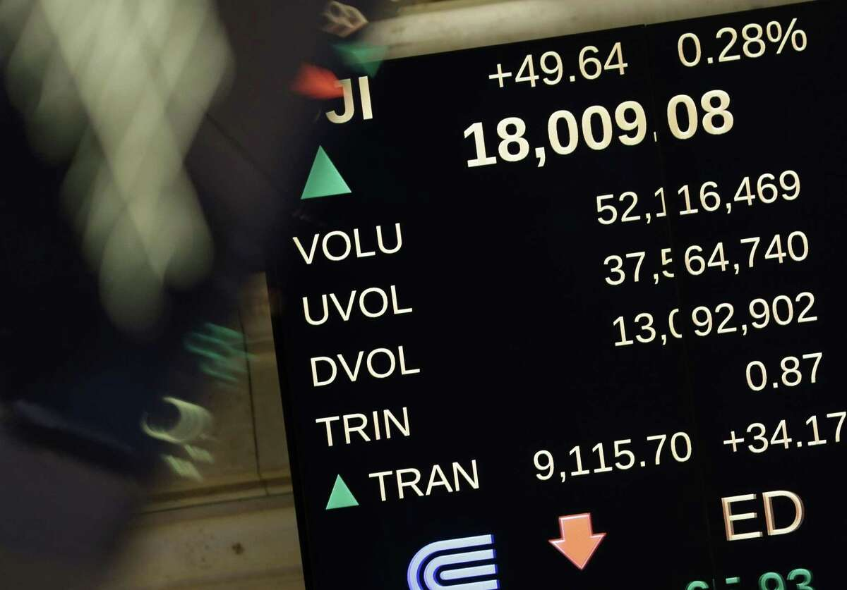 An electronic displays shows the Dow Jones Industrial Average above 18,000 on the floor of the New York Stock Exchange in New York, Tuesday. The Dow Jones industrial average broke through 18,000 points for the first time Tuesday as the stock market continued a late-year march to record highs.
