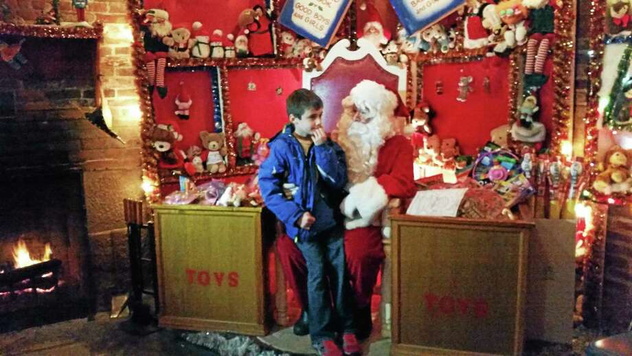 Amanda Webster/Register Citizen  Nine-year-old Lance Bagley thinks of what to ask Santa for Christmas during his visit to Christmas Village on Wednesday. The village, which opened in early December, closed for the season on Christmas Eve. Photo: Journal Register Co.