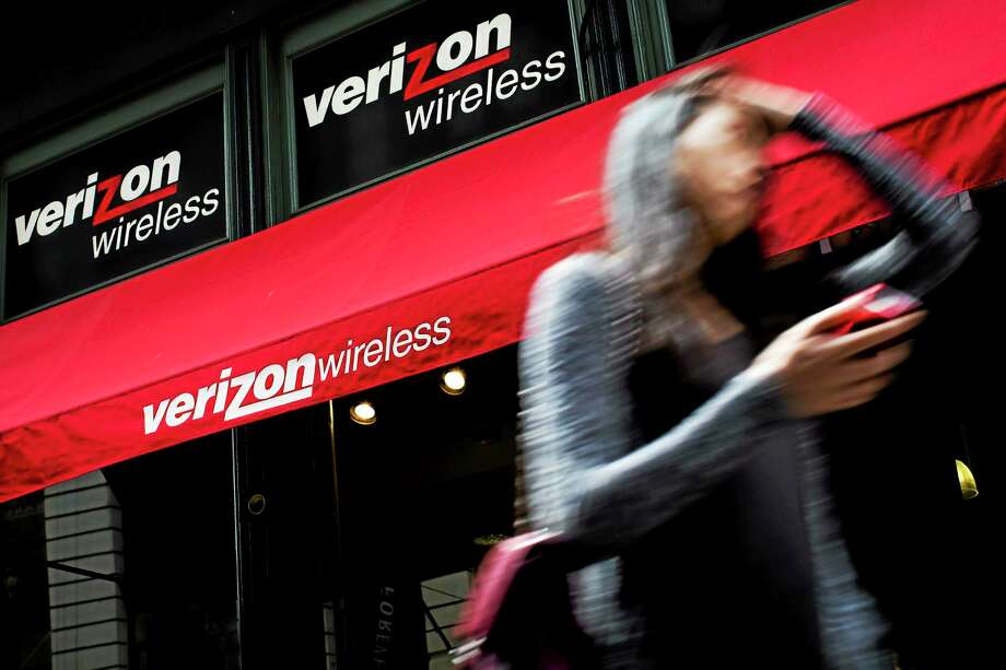 In this Thursday, June 6, 2013, file photo, a pedestrian uses her cell phone as she passes a Verizon Wireless store on Broadway in Lower Manhattan, in New York. Verizon Communications Inc. reports quarterly financial results before the market opens on Tuesday, Jan. 21, 2014. Photo: John Minchillo—File—The Associated Press  / A20132013