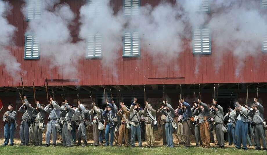 Confederate soldiers fire their weapons. Re-enactors from the 2nd Florida infantry recreate the assault and retreat of the 1st North Carolina from the Battle of Culp's Hill Friday, June 28, 2013 at The Daniel Lady Farm. (Public Opinion, Markell DeLoatch)