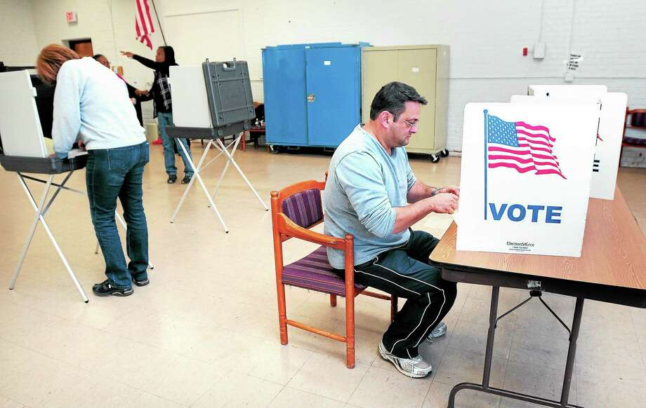 Chris LaTorraca, right, votes at the Keefe Center in Hamden Tuesday. Photo: Arnold Gold — New Haven Register