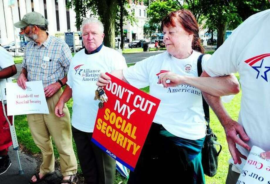Arnold Gold/New Haven Register Connecticut AFL-CIO president John Olsen (center) and Cynthia Pincus Russell (right) of Stratford lock arms to protest the proposed chained CPI for Social Security on the New Haven Green on 7/2/2013.