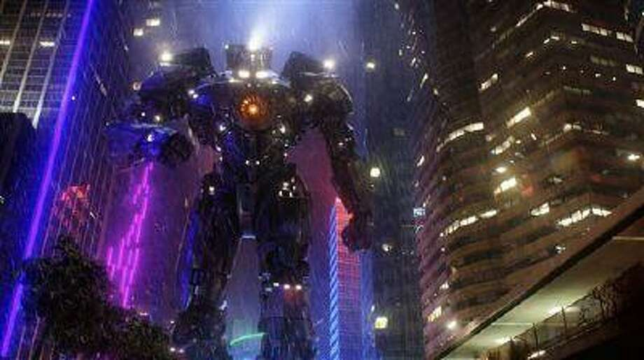 """This film publicity image released by Warner Bros. Pictures shows the Gipsy Danger robot in a scene from """"Pacific Rim."""" """"Pacific Rim"""" fulfills a very basic boyhood fantasy: big ol' robots and giant monsters slugging it out. The concept to Guillermo del Toro's """"Godzilla""""-sized film is about as simple as it gets, but actually constructing such mammoth creations is a far more arduous undertaking. (AP Photo/Warner Bros. Pictures) Photo: AP / Warner Bros. Pictures"""
