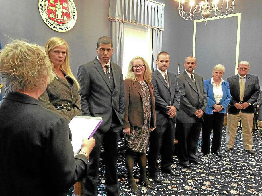 Winsted Town Clerk Sheila Sedlack swears in the new Winsted Board of Selectman. From left, Mayor Lisa Smith, Jorge Pimentel, Candace Bouchard, Daniel Langer, Robert Vogt, A. Candy Perez and George Closson. Perez, who along with Closson are the lone Democrats on the new board, was named second selectman. Photo: Mercy Quaye—Register Citizen