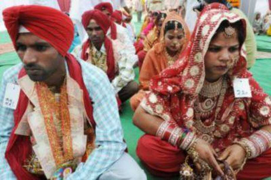 Indian brides sit with their grooms during a mass marriage ceremony on April, 13 2009.