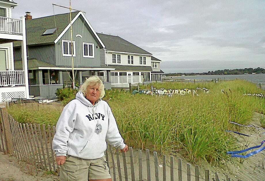 In this Oct. 16, 2013 photo, Paige Herman, president of the Fairfield Beach Residents Association, poses in front of her house on the beach in Fairfield, Conn. The association is giving away thousands of plants to encourage residents to create or expand sand dunes, and Herman thinks the little dune in front of her house likely prevented even worse damage than she suffered during Superstorm Sandy. The growing interest in building berms and dunes faces obstacles, including concerns about obstructed views in a swath of land with some of the nation's priciest real estate. (AP Photo/John Christoffersen) Photo: AP / AP