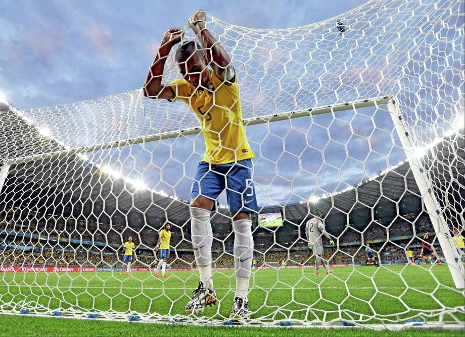 Brazil's Fernandinho reacts after Germany's Toni Kroosduring scored his side's third goal during the World Cup semifinals Tuesday at the Mineirao Stadium in Belo Horizonte, Brazil. Germany won 7-1. Photo: Natacha Pisarenko — The Associated Press  / AP
