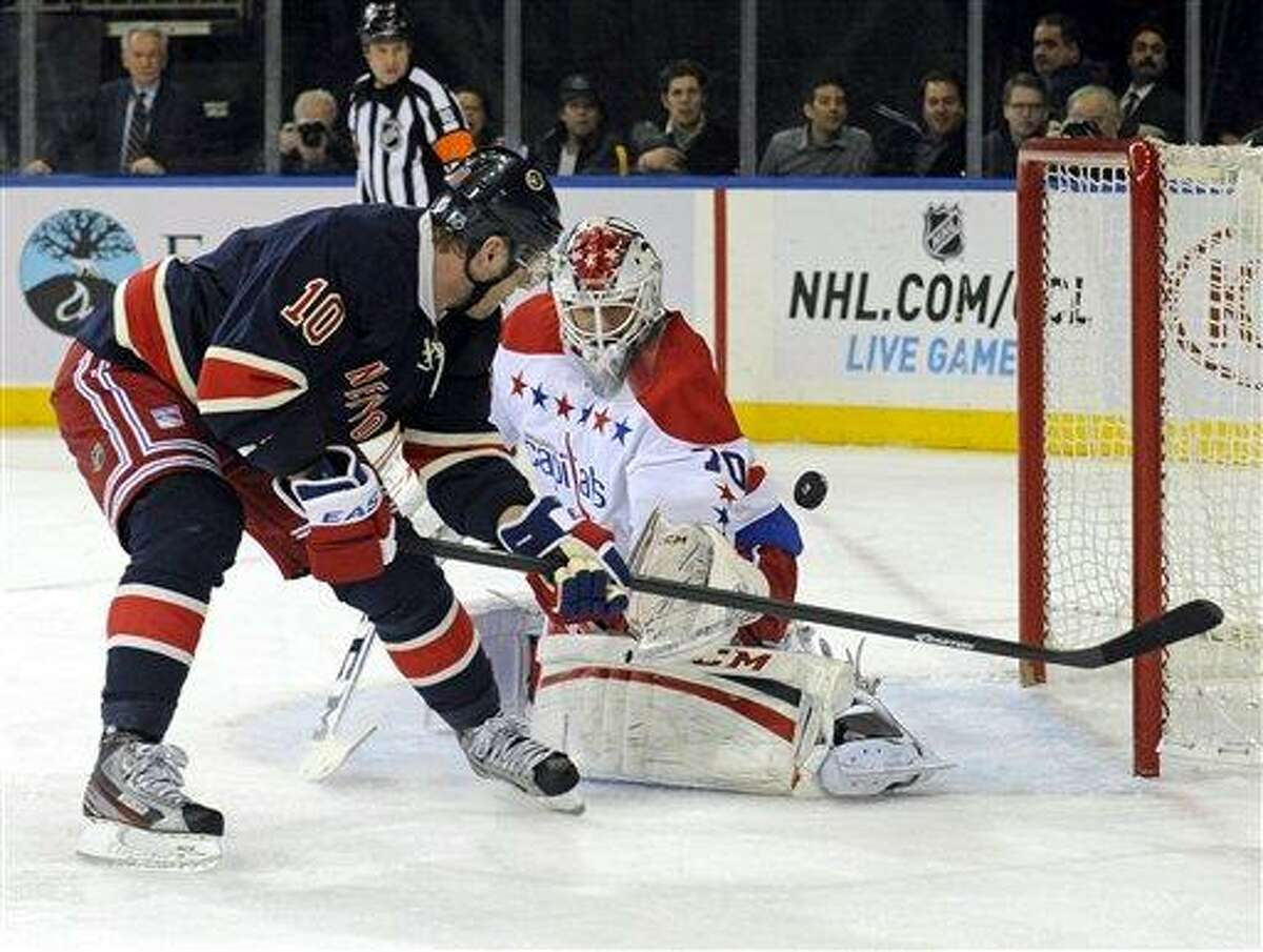 Washington Capitals goaltender Braden Holtby, right, makes a save on a shot by New York Rangers' Marian Gaborik, of Slovakia, during the second period of an NHL hockey game Sunday, March 24, 2013, at Madison Square Garden in New York. (AP Photo/Bill Kostroun)