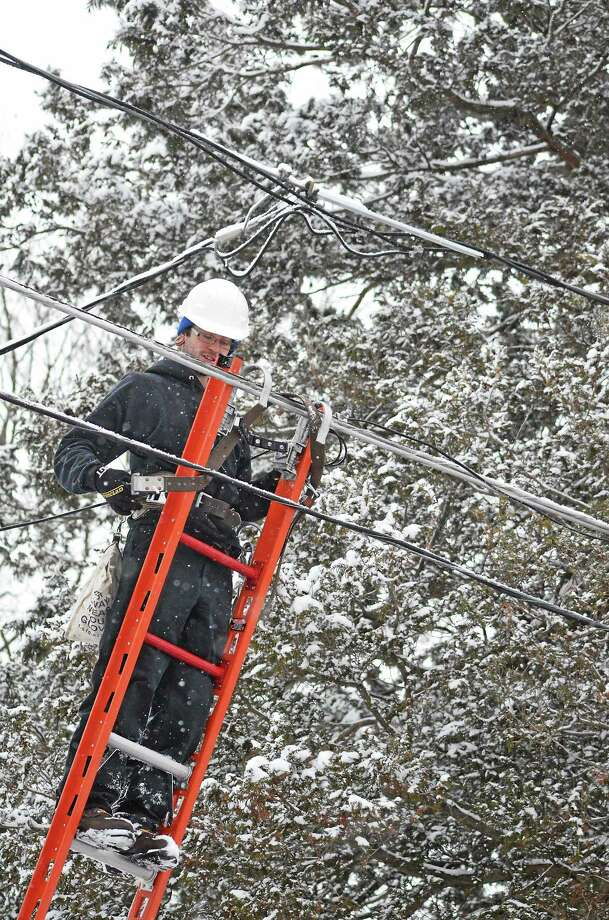 Stephen Ruiz works on a line for Optimum Cable in Torrington on Monday during the snowfall. Photo: John Berry—The Register Citizen