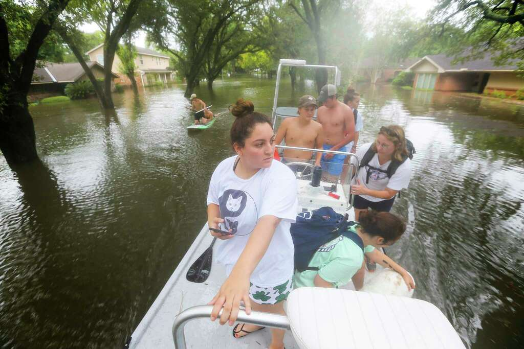 Savina Rodriquez surveys the expanse of a flooded Runnymeade Street after being evacuated by boat to the Kroger on W. Belfort Street at S. Post Oak Blvd. during extreme flooding in Meyerland, Sunday, Aug. 27, 2017, in Houston. Photo: Mark Mulligan, Houston Chronicle / 2017 Mark Mulligan / Houston Chronicle