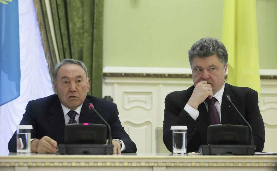Kazakhstan's President Nursultan Nazarbayev, left, and Ukrainian President Petro Poroshenko address the media in the Ukrainian Presidential office in Kiev, Ukraine, Monday, Dec. 22, 2014. (AP Photo/Efrem Lukatsky) Photo: AP / AP