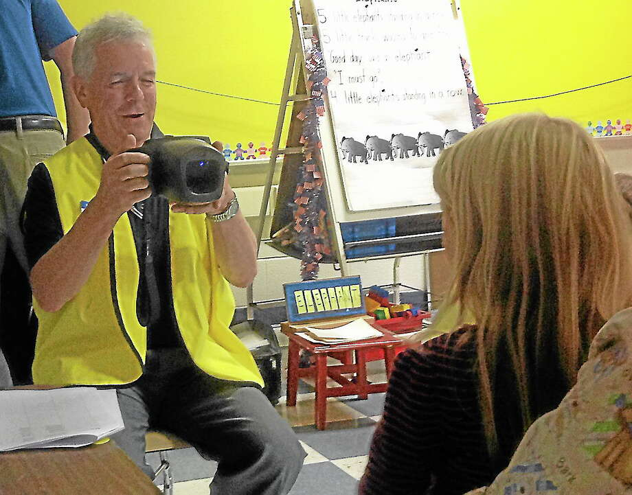 Submitted photo. Burlington Lion's Club member Wayne Frombach gave children eye screenings at Lake Garda School. Photo: Journal Register Co.
