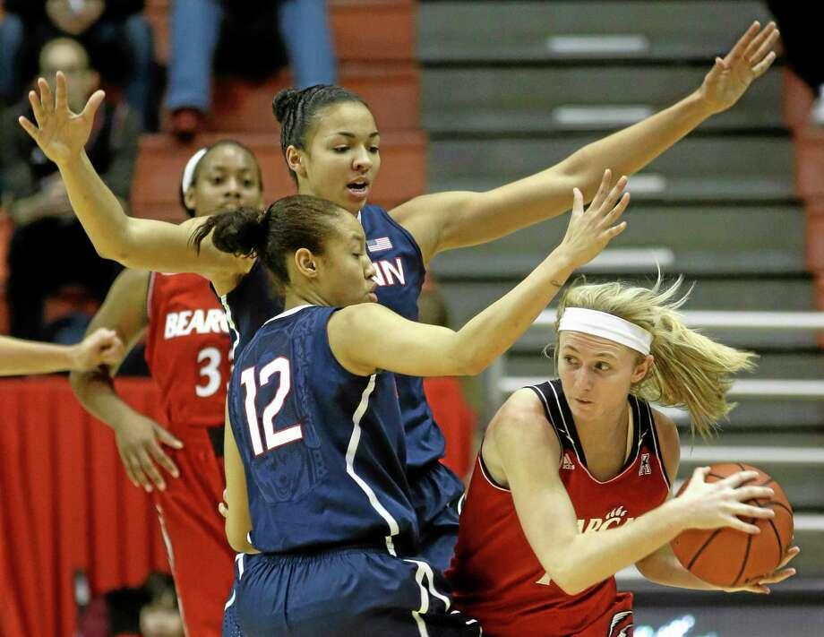 Cincinnati guard Kayla Cook, right, looks to pass around UConn guard Saniya Chong (12) and center Kiah Stokes on Saturday. Photo: Al Berhman — The Associated Press  / AP
