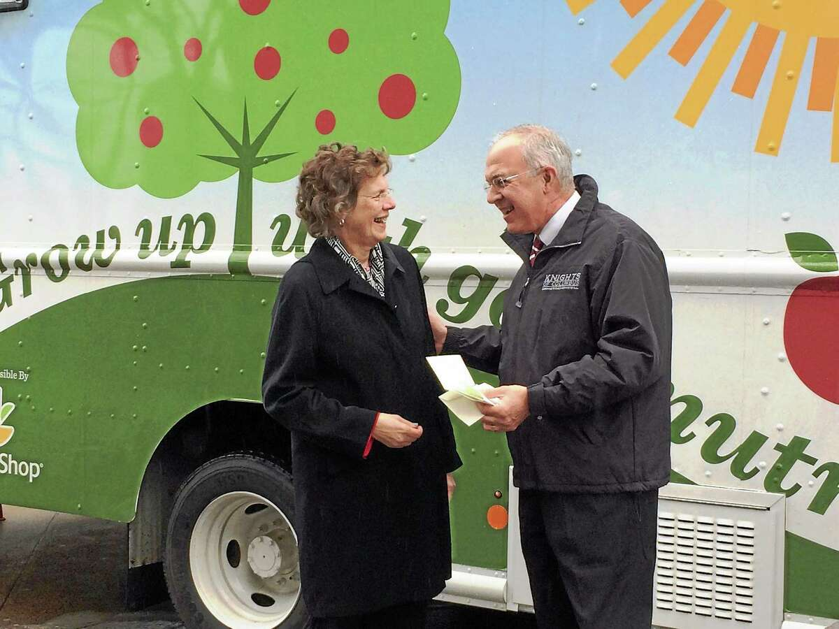 Knights of Columbus Supreme Knight Carl Anderson and Connecticut Food Bank CEO Nancy Carrington stand in front of a special refrigerated food bank truck Tuesday at the Knights of Columbus headquarters in New Haven. The group donated $100,000 to the food bank Tuesday.