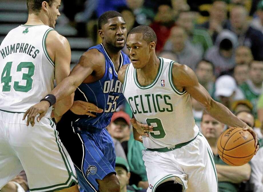 Celtics guard Rajon Rondo (9) looks for an opening around Magic guard E'Twaun Moore (55) in the fourth quarter Sunday. Photo: Steven Senne — The Associated Press  / AP