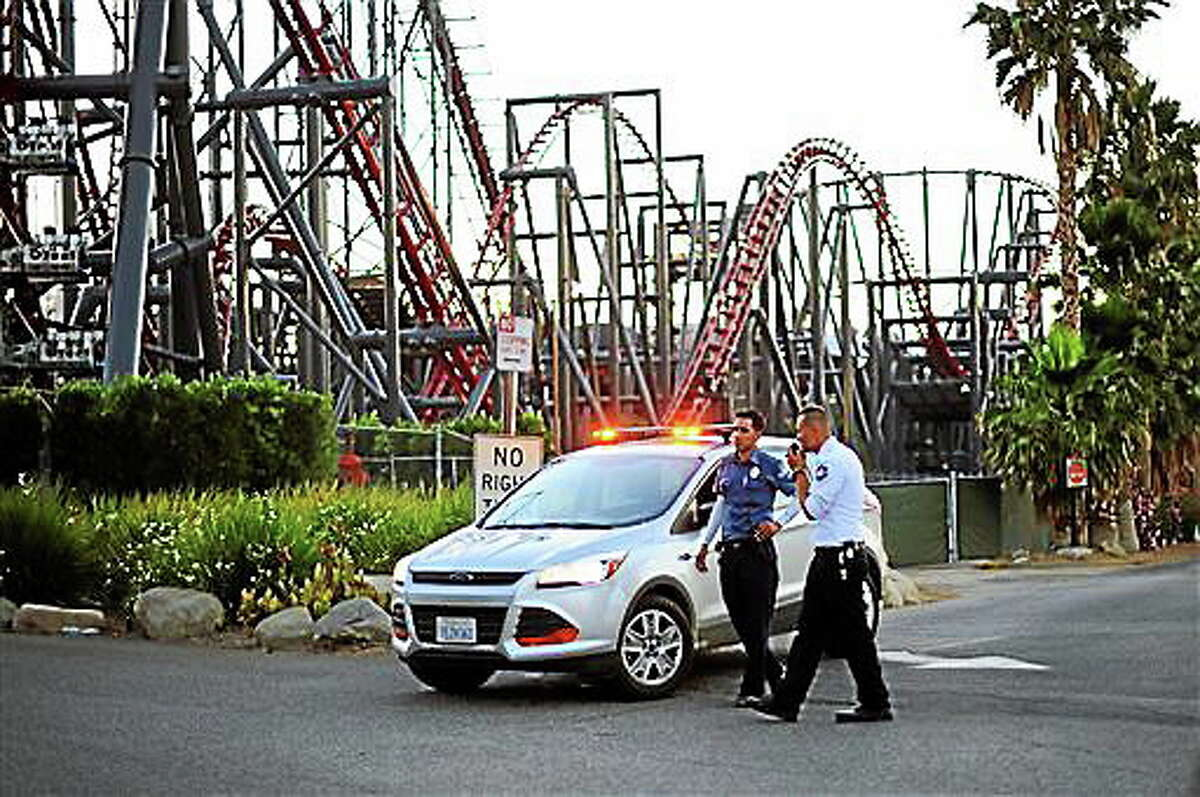 Members of the Six Flags Magic Mountain amusement park security staff monitor the situation at the exit of the park after riders were injured on the Ninja coaster Monday, July 7, 2014, in Valencia, Calif. The roller coaster hit a tree branch dislodging the front car, leaving four people slightly injured and keeping nearly two dozen summer fun-seekers hanging 20 to 30 feet in the air for hours as day turned to night. Two of the four people hurt on the Ninja coaster were taken to the hospital as a precaution, but all the injuries were minor, fire and park officials said.