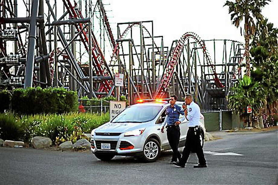 Members of the Six Flags Magic Mountain amusement park security staff monitor the situation at the exit of the park after riders were injured on the Ninja coaster Monday, July 7, 2014, in Valencia, Calif. The roller coaster hit a tree branch dislodging the front car, leaving four people slightly injured and keeping nearly two dozen summer fun-seekers hanging 20 to 30 feet in the air for hours as day turned to night. Two of the four people hurt on the Ninja coaster were taken to the hospital as a precaution, but all the injuries were minor, fire and park officials said. Photo: Associated Press  / Los Angeles Daily News
