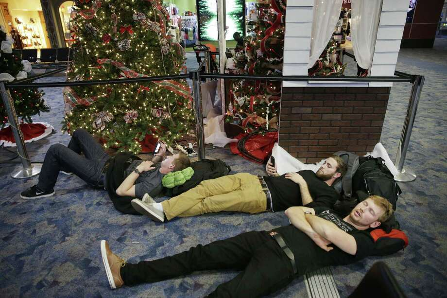 From left, Nick Burton, Clancy Sloan and Graham Anderson rest while waiting for their flight at McCarran International Airport Sunday, Dec. 21, 2014, in Las Vegas. Photo: (AP Photo/John Locher) / AP