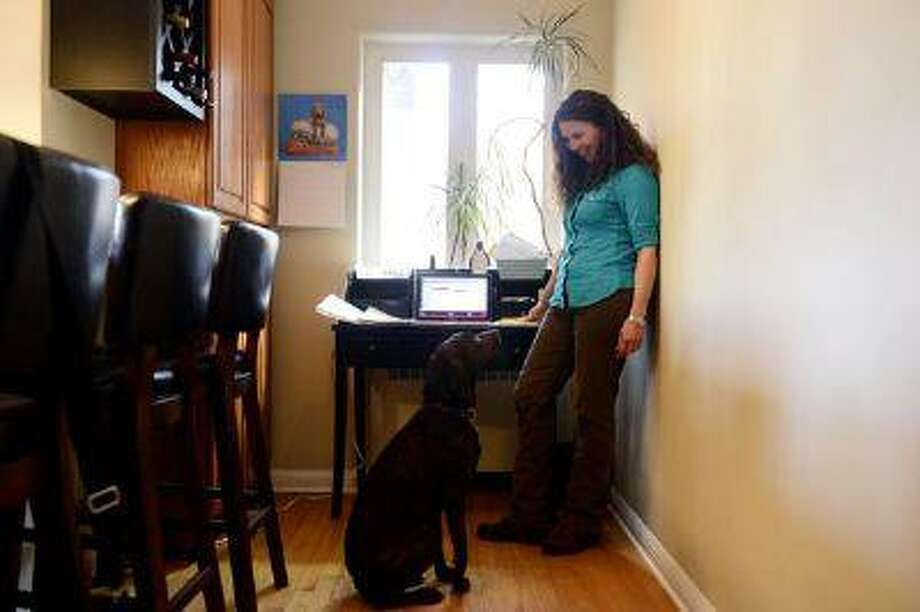 """Rebecca Olgeirson talks to dog her dog, Annie, near her """"mom"""" desk in the kitchen. Olgeirson is taking control of her clutter problem. Photo: DP / Copyright - 2013 The Denver Post, MediaNews Group."""