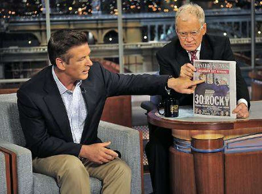 """Alec Baldwin points to a photo of himself on the front page of the New York Daily News as he talks with host David Letterman about is altercation with a photographer during a taping of """"Late Show with David Letterman"""" in New York. (AP Photo/CBS, John Paul Filo)"""