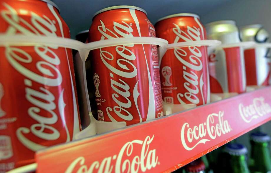 In this June 30, 2014 photo cans of Coca-Cola soda pop are shown in the refrigerator inside of Chile Lindo in San Francisco. San Francisco and Berkeley are aiming to become the first U.S. cities to pass per-ounce taxes on sugary drinks. (AP Photo/Jeff Chiu) Photo: AP / AP