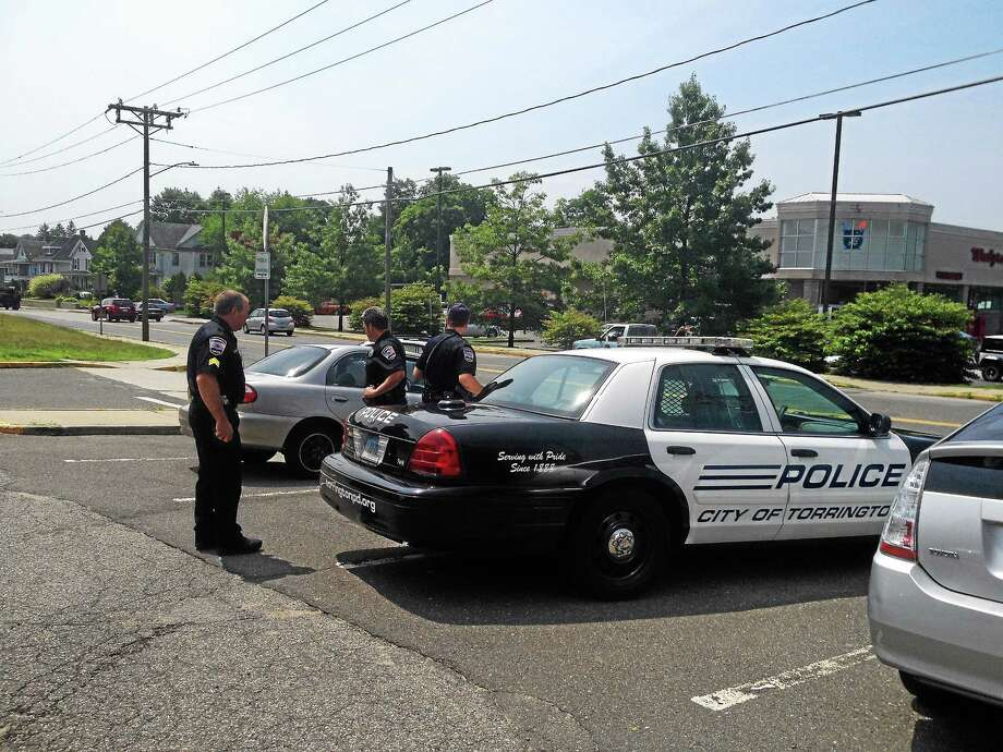 Torrington police officers stand near a cruiser with a man who had been placed in custody after a small amount of pot was found in his car, which was parked at police headquarters Tuesday. Photo: Esteban L. Hernandez — The Register Citizen