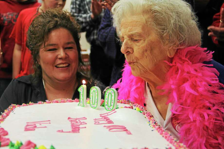 Viola Vienot, right, blows the candles from her birthday cake as her granddaughter,  Selena Lefebvre, looks on during Veinot's 100th birthday party at Workman Apartments on Feb. 2, 2014, in Torrington. Photo: Esteban L. Hernandez—Register Citizen