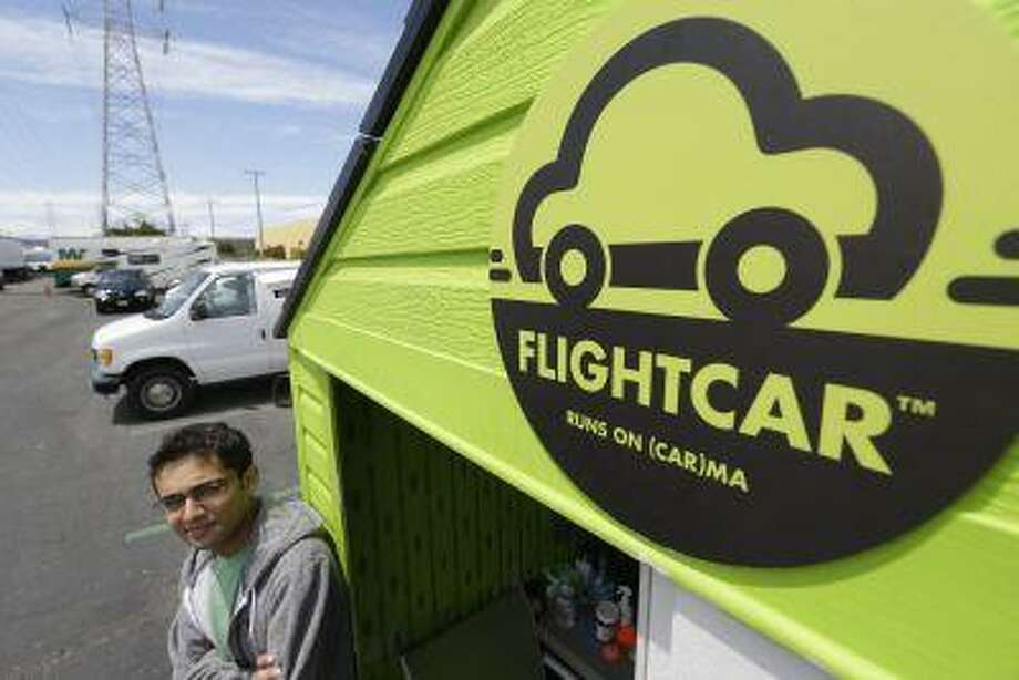 In this photo taken Tuesday, June 11, 2013 Flightcar CEO Rujul Zaparde, poses outside a small rental shack on their lot in Burlingame, Calif. A San Francisco Bay area startup company founded by three teenage Ivy League dropouts is trying to change the airport car rental business. FlightCar rents out people's personal vehicles while they are traveling, giving them a share of the proceeds and free airport parking in exchange. But the company's rosy outlook does have some thorns. San Francisco's City Attorney has sued FlightCar, accusing it of unfair competition. (AP Photo/Eric Risberg) Photo: AP / AP