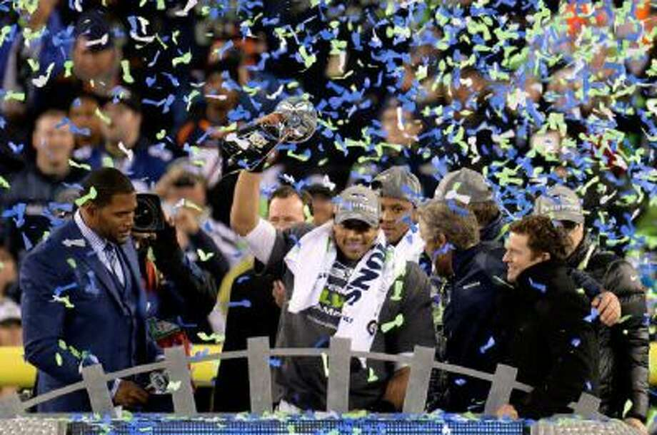 Seattle Seahawks quarterback Russell Wilson (3) holds up the Vince Lombardi Trophy after the Seahawks defeated the Broncos 43 to 8.