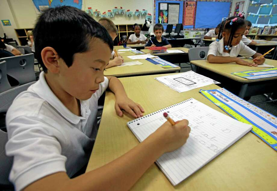 A student practices his cursive in this archive photo, something that's seen less and less in American schools, as technology replaces traditional means of learning in the classroom. Photo: File Photo  / AP