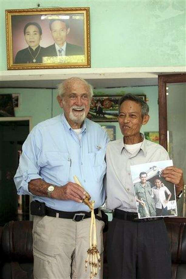Dr. Sam Axelrad, left, displays the bones of an arm belonging to former North Vietnamese soldier Nguyen Quang Hung, right, at Hung's house in the town of An Khe, Gia Lai province, Vietnam on Monday July 1, 2013. In October 1966 Axelrad amputated Hung's arm after the soldier was shot in the arm in an ambush by American troops in the coastal province of Binh Dinh in the former South Vietnam. After decades of silence, the two veterans resumed contact after a Vietnamese journalist wrote an article in a newspaper last year about Axelrad's search for Hung, prompting Hung's brother in law to contact the newspaper's editors. (AP Photo/Thanh Nien Newspaper, Kha Hoa) Photo: AP / Thanh Nien Newspaper