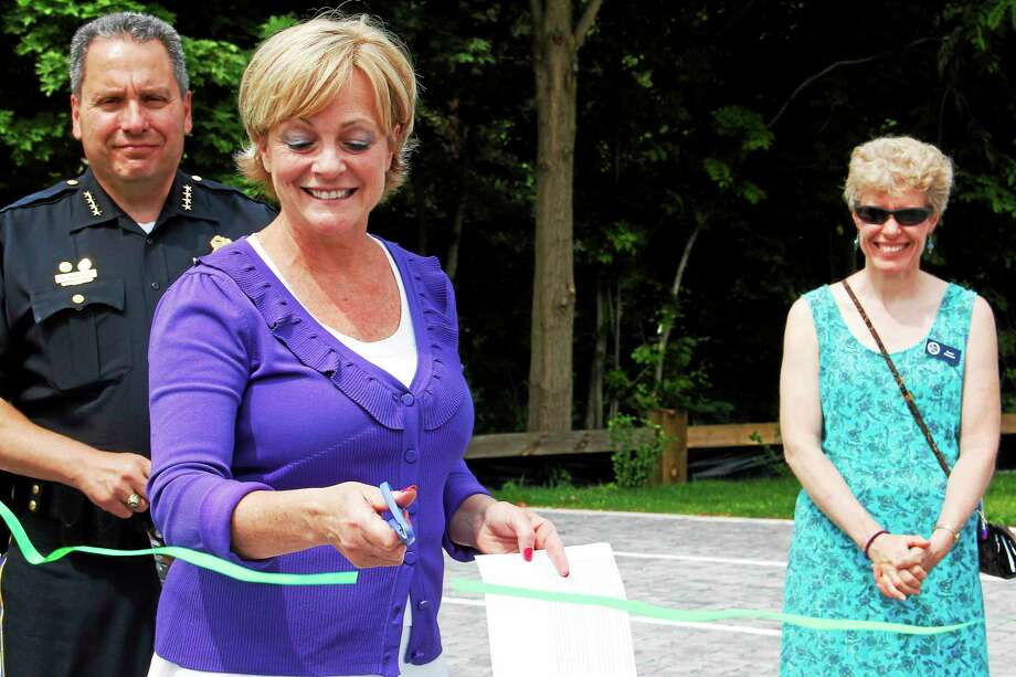 Torrington Mayor Elinor Carbone cuts a ribbon to commemorate a new municipal parking lot on the corner of Main and North Elm streets Tuesday. Behind her are Police Chief Michael Maniago, left, and Susan Peterson, a watershed manager with the state Department of Energy and Environmental Protection. Photo: Esteban L. Hernandez — The Register Citizen