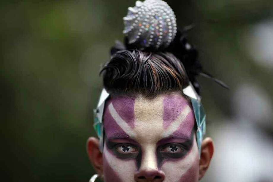 A person wearing face paint and eye contacts attends a gay pride parade in Caracas, Venezuela, Sunday, June 30, 2013.  Gays, lesbians and transgenders are participating in gay pride parades worldwide in late June as part of annual demonstrations for equal rights and against discrimination.  (AP Photo/Ariana Cubillos) Photo: ASSOCIATED PRESS / AP2013