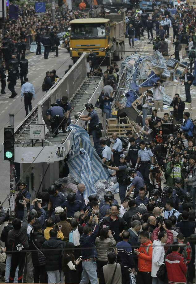 Police officers take down a tent on top of a train station on a main road in the occupied areas at Causeway Bay district in Hong Kong Monday, Dec 15, 2014. Hong Kong police tore down barricades, folded up tents and arrested some protesters Monday at a third and final pro-democracy protest camp, ending demonstrations that blocked traffic in the southern Chinese city's streets for two and a half months. (AP Photo/Vincent Yu) Photo: AP / AP