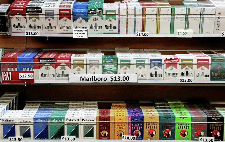 In this March 18, 2013 file photo, cigarette packs are displayed at a convenience store in New York. On Wednesday, Oct. 30, 2013, law makers in New York City voted to raise the cigarette-buying age from 18 to 21. Photo: Mark Lennihan—FILE—The Associated Press  / AP
