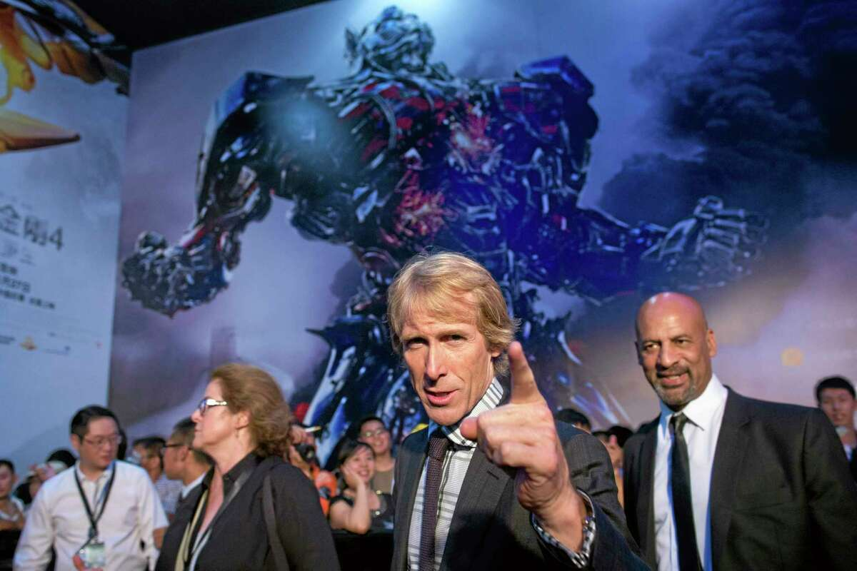 """Director Michael Bay, center, gestures to fans June 23 as he attends the premiere of movie """"Transformers: Age of Extinction"""" at a theatre in Beijing, China."""