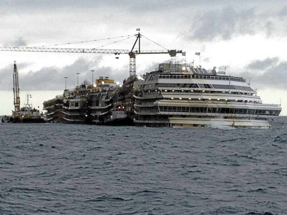 The Costa Concordia cruise liner lies in the waters of the Giglio Island, Italy, Thursday, Jan. 23, 2014. Experts boarded the Costa Concordia cruise liner to investigate whether there is more to the shipís sinking than is contained in prosecutorsí case against its captain. A team on Thursday examined the bridge of the cruise liner that sank Jan. 13, 2012 with thousands aboard, killing 32, to investigate if any factors beyond human error contributed to the shipwreck. Experts are to return next month to look at the linerís emergency generator. A judge granted a joint request for the onboard evaluation to collect evidence sought by Capt. Francesco Schettinoís defense and a consumer group representing victims. So far, Schettino is the only person being tried although his defense and others contend that Costa Crociere SpA, the shipís owner, bears some responsibility. (AP Photo/Luigi Navarra) Photo: AP / AP