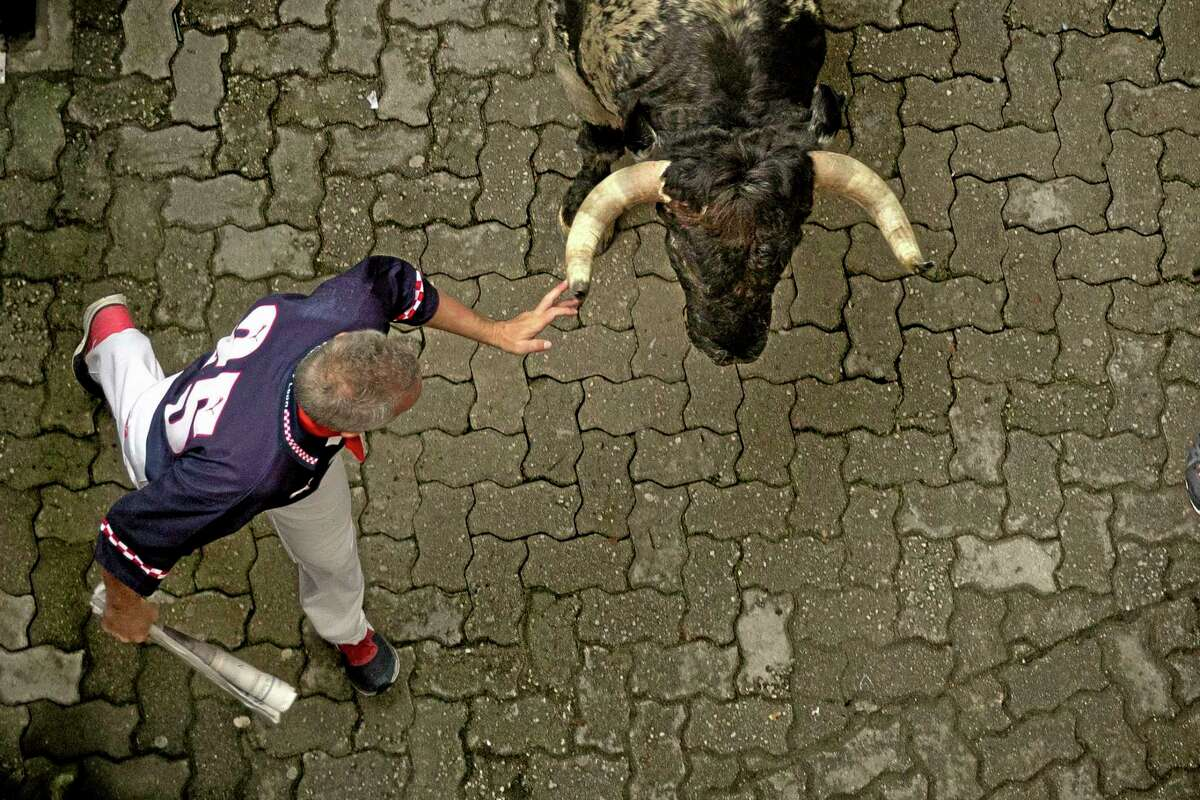 """A running reveler touches the horn of a Torrestrella's ranch fighting bull during the running of the bulls of the San Fermin festival, in Pamplona, Spain, Monday. Revelers from around the world arrive in Pamplona every year to take part on some of the eight days of the running of the bulls glorified by Ernest Hemingway's 1926 novel """"The Sun Also Rises."""""""