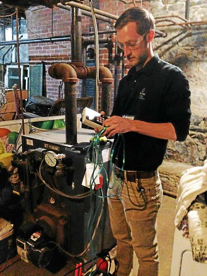 Contributed photo Next Step Living home energy solutions adviser Chris Haringa monitors the emissions levels in Mayor Candace Bouchard's basement. Photo: Journal Register Co.