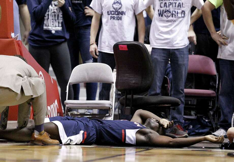UConn guard Terrence Samuel is attended to by a trainer after suffering an injury against Duke on Thursday. Photo: Julio Cortez — The Associated Press  / AP