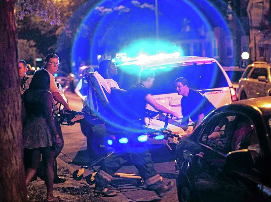 In this Sunday, July 6, 2014 photo, a man is wheeled on a stretcher after being shot in the leg on Chicago's South Side. The Fourth of July weekend was a bloody one in Chicago, where at least nine people were shot to death and at least 60 others were wounded. Photo: Associated Press  / Sun-Times Media