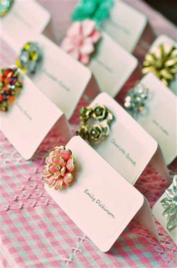 In this undated publicity photo provided by the website Intimate Weddings, vintage brooches are pinned to wedding-reception place cards as an example of creative DIY projects that help guests navigate seating assignments. (AP Photo/Intimate Weddings, Christina Friedrichsen) Photo: AP / Intimate Weddings