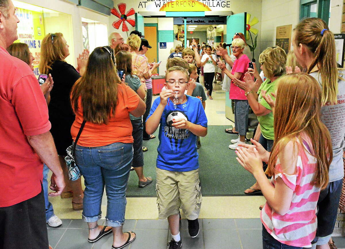 5th grader Nick Austin, 11, blows bubbles as he walks through the halls Waterford Village Elementary School in Michigan for a clap-out on the last day of school on June 13.
