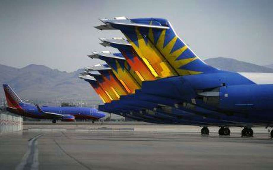 In this Thursday, May 9, 2013, photo, a Southwest airline taxis by parked Allegiant Air jetliners at McCarran International Airport in Las Vegas. While other U.S. airlines have struggled with the ups and downs of the economy and oil prices, tiny Allegiant Air has been profitable for 10 straight years. (AP Photo/David Becker) Photo: ASSOCIATED PRESS / AP2013