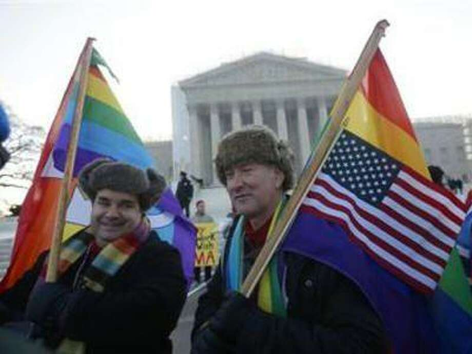 Marcus, left, and Daniel German-Dominguez stand outside the Supreme Court in Washington, Tuesday, March 26, 2013, before the court's hearing on California's voter approved ban on same-sex marriage. Photo: AP / AP